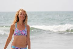A young and beautiful girl, wearing sunglasses, in a beautiful separate swimsuit and blond hair, stands and smiles against the royalty free stock photography