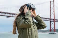 Young beautiful girl wearing virtual reality glasses. 25th of April bridge in Lisbon in the background. The concept of Stock Images