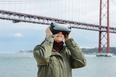 Young beautiful girl wearing virtual reality glasses. 25th of April bridge in Lisbon in the background. The concept of Royalty Free Stock Image