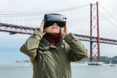 Young beautiful girl wearing virtual reality glasses. 25th of April bridge in Lisbon in the background. The concept of. Modern technologies and their use in stock photo
