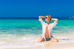 Young beautiful girl in wet white shirt  on the beach. Blue trop Stock Photography