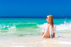 Young beautiful girl in wet white shirt  on the beach. Blue trop. Ical sea in the background Stock Images