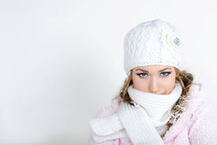 The young beautiful girl in a white cap. And a scarf with snowflakes on hair Royalty Free Stock Photos