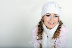 The young beautiful girl in a white cap. And a scarf with snowflakes on hair Royalty Free Stock Photography