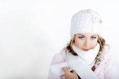 The young beautiful girl in a white cap. And a scarf with snowflakes on hair Stock Photos