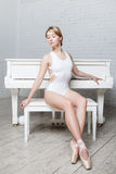 Young beautiful girl in white dance leotard and Pointe shoes, ballet dancer. Sits, background piano, style, grace Stock Photos
