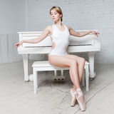 Young beautiful girl in white dance leotard and Pointe shoes, ballet dancer. Sits, background piano, style, grace Stock Image