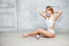 Young beautiful girl in white dance leotard and Pointe shoes, ballet dancer. Sitting in a luxurious white chair in a vintage style Stock Photos