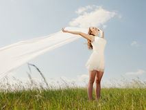 Spring Girl. The young beautiful girl in a white dress enjoys a wind, the sun royalty free stock photography