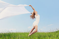 Spring Girl. The young beautiful girl in a white dress enjoys a wind, the sun Stock Photos