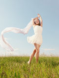 Spring Girl. The young beautiful girl in a white dress enjoys a wind, the sun stock photo