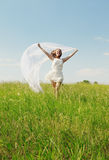 Spring Girl. The young beautiful girl in a white dress enjoys a wind, the sun stock photography