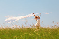 Spring Girl. The young beautiful girl in a white dress enjoys a wind, the sun Stock Images
