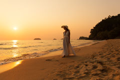 Young beautiful girl in a white dress and straw hat on a tropica Royalty Free Stock Images