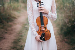 Young beautiful girl in a white dress under tree holding a violin in hands. Stock Photography