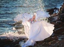 Young beautiful girl in a white dress with wings on the beach. Blonde woman on the rocks with the sea raging and powerful Stock Photos