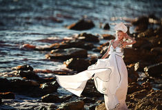 Young beautiful girl in a white dress with wings on the beach Royalty Free Stock Photo