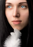 Young beautiful girl with a white feather Stock Photo