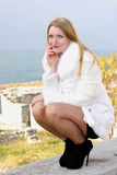 The young beautiful girl in a white fur coat Stock Photos