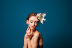 Young beautiful girl with a white lily on blue Stock Image