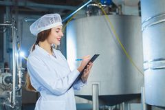 A young beautiful girl in white overalls makes notes in a tablet on the background of equipment of a food processing plant. Quality control in production royalty free stock photography