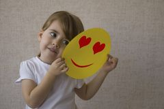 Young beautiful girl in white shirt smiles and holds in her hands a yellow paper with a draw heart. With love. Young beautiful girl in white shirt smiles and Royalty Free Stock Photography