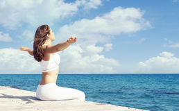 Young and beautiful girl in white sportswear doing yoga on a woo Royalty Free Stock Photos