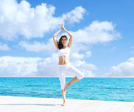 Young and beautiful girl in white sportswear doing yoga on a woo Royalty Free Stock Photography