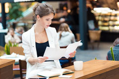 Young, beautiful girl in a white suit, sitting in the cafe at th Stock Photography