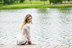 Young beautiful girl in a white tunic sits on a wooden pier on t Stock Image