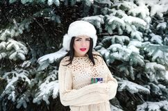 Young beautiful girl in the winter park with a cup of coffee. Near fir trees Stock Image