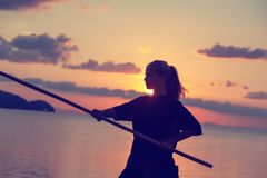 Young beautiful girl woman blond doing kung fu with bamboo stick on the seashore at sunset, fight. Young beautiful girl woman blond doing kung fu with bamboo stock image