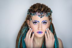 Woman with dreads. Young beautiful girl woman with brown, blue dreadlocks. Stylish volume hair-do, professional make-up art, rhinestones crystals. Large tiara Stock Photos