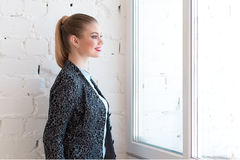 Young beautiful girl or woman smiling and looking at the window. Young beautiful girl or woman is standing next to a  white wall, smiling and looking at the Royalty Free Stock Image