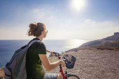 Young beautiful girl woman travels by bicycle on a mountain land stock image