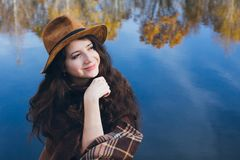 Girl on a wooden old bridge on a lake. Young beautiful girl on a wooden old bridge on a lake in the picturesque autumn forest. Toning Royalty Free Stock Photo