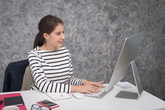 Young beautiful girl working on the laptop at the office royalty free stock photo