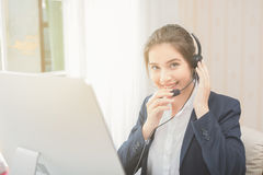 Young beautiful girl working at a laptop in a small medium enterprise Royalty Free Stock Photo