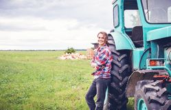 Young beautiful girl working on a tractor in the field, unusual work for women, a gender equality concept. Young beautiful girl working on a tractor in the field royalty free stock images