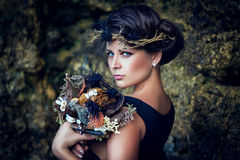 Young beautiful girl with a wreath in the sea theme, holding a b Stock Image