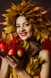 The young beautiful girl in a wreath of yellow leaves with a basket of fruit Royalty Free Stock Photo