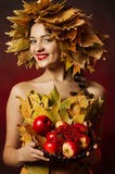 The young beautiful girl in a wreath of yellow leaves with a basket of fruit Royalty Free Stock Photos