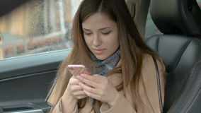Young beautiful girl writes sms, sitting in the car in the front seat. Smiling reading good news. stock footage