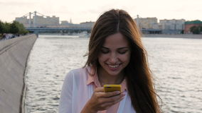 Young beautiful girl writes SMS on your smartphone. Very happy, slow motion stock footage