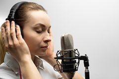 Young beautiful girl writes vocals, radio, voiceover tv, reads poetry, blog, podcast in studio on studio microphone in headphones. On white background stock image