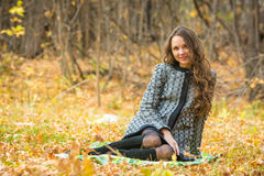 Young beautiful girl in a yellow coat sitting on fallen leaves in the forest Royalty Free Stock Images
