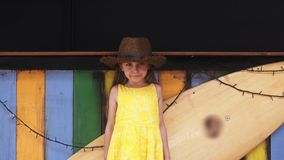 Little Beautiful girl in yellow dress stands near surf board. Young Beautiful girl in yellow dress stands near surf board in 4K stock footage