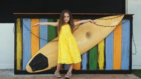 Little Beautiful girl in yellow dress stands near surf board. Young Beautiful girl in yellow dress stands near surf board in 4K stock video footage
