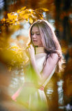 Young beautiful girl in a yellow dress in the woods. Portrait of romantic woman in fairy forest. Stunning fashionable teenager Royalty Free Stock Photography
