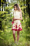 Young beautiful girl in a yellow dress in the woods. Portrait of romantic woman in fairy forest. Stunning fashionable teenager Stock Photo